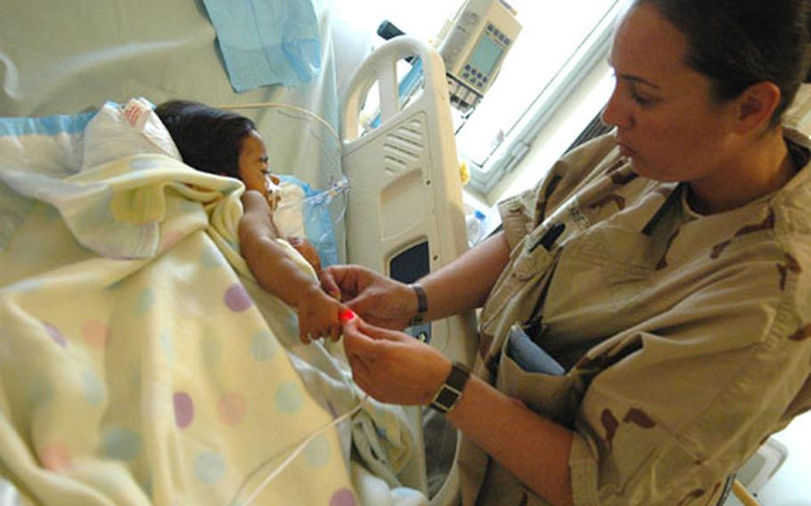 Army medic Michelle Chavez, 29, of Huntington Beach Calif., checks the temperature of a young Iraqi at the Ibn Sina Hospital intensive care ward in Baghdad's Green Zone on Tuesday.