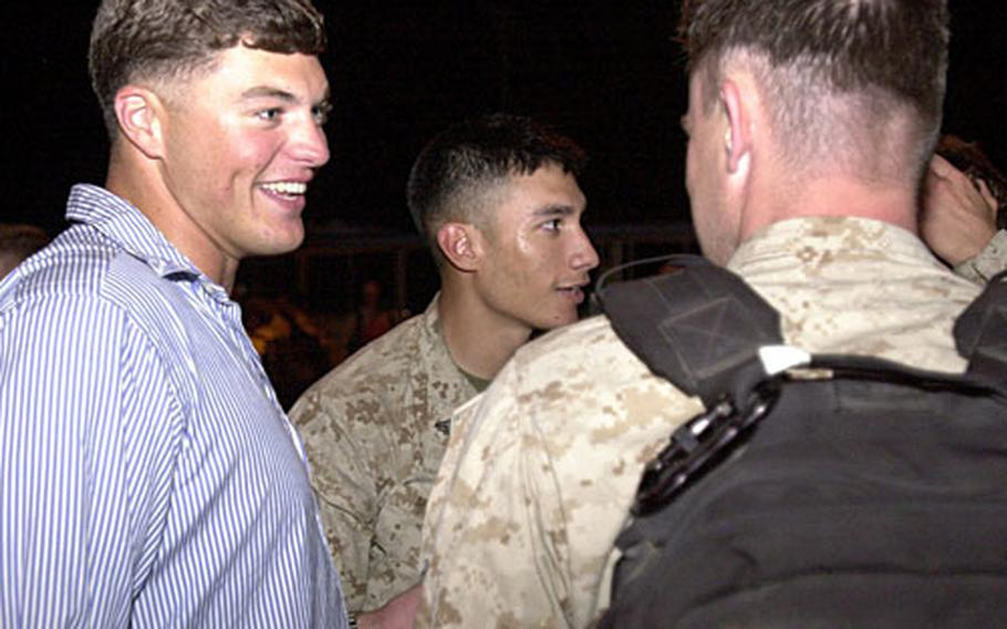 Sgt. Sam Meek, left, greets buddies that he has not seen since he was wounded in Iraq in January and sent to a burn center in Texas. He and two other 3rd Recon Marines, wounded and returned to the States during the unit's deployment to Iraq, flew to Okinawa to be part of Tuesday's welcome-home reception at Camp Schwab.