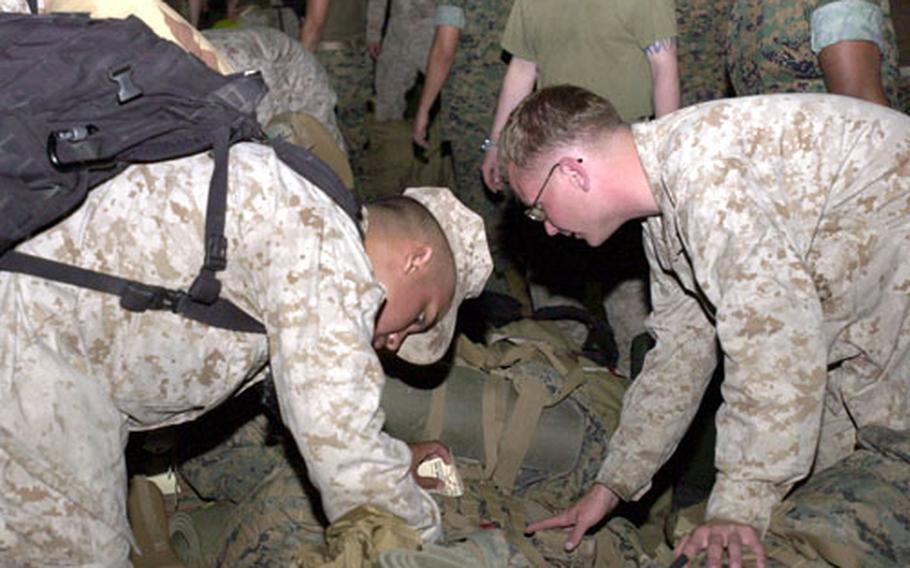 Sailors and Marines search through gear looking for their own packs after returning to Camp Schwab late Tuesday evening.