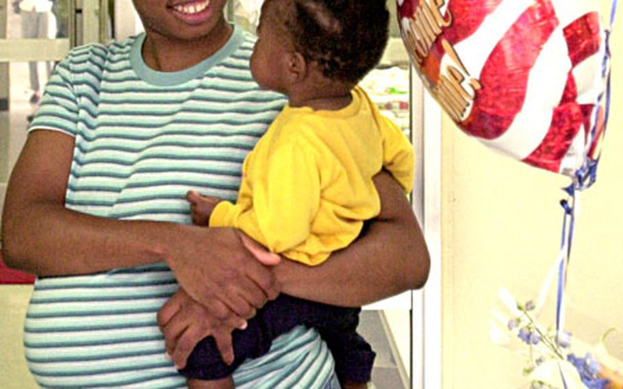 """Rasheeda Stokes and son Christian, 13 months, wait for the return of Sgt. Z. B. Stokes Tuesday evening. Rasheeda, who is due in two weeks, said she was worried that the """"baby would come before (her husband) came back."""""""