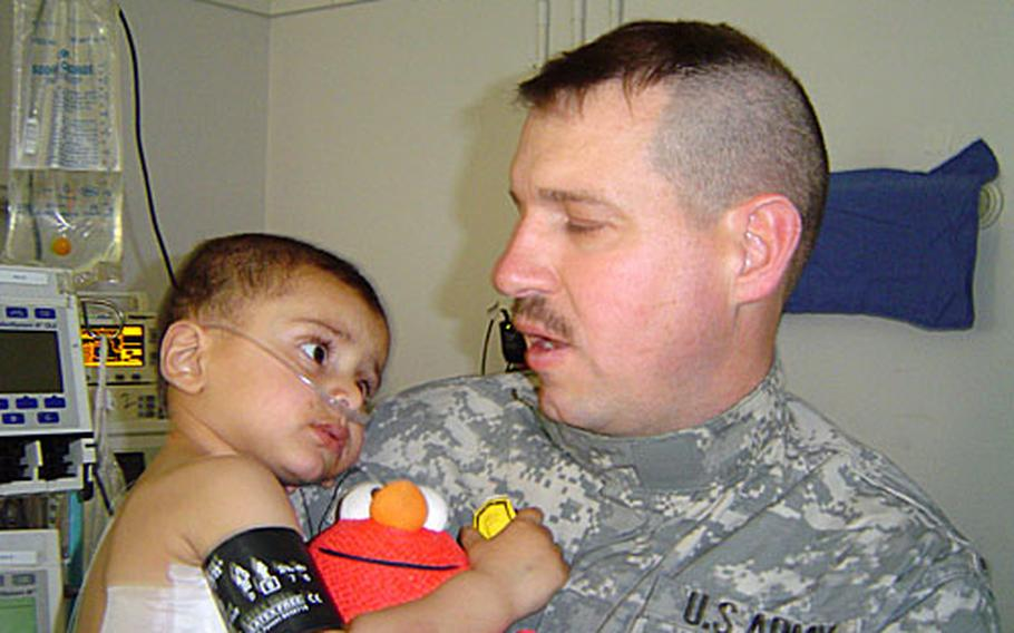 Settles holds one of the small patients at the hospital, who in turn holds one of Settles' toy donations.