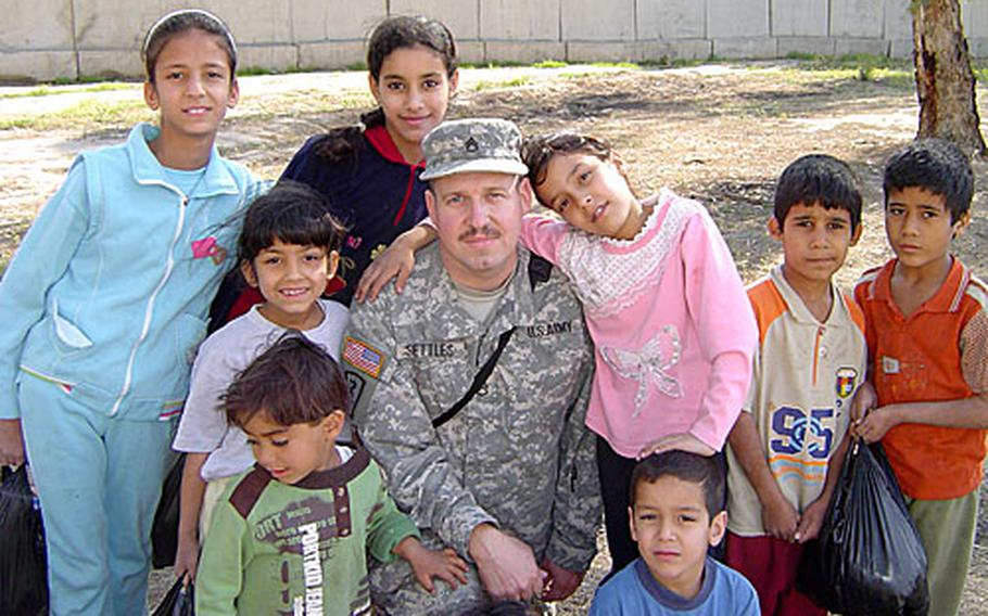 Settles poses with some of the kids to whom he gives donations of toys, school supplies and other treats.