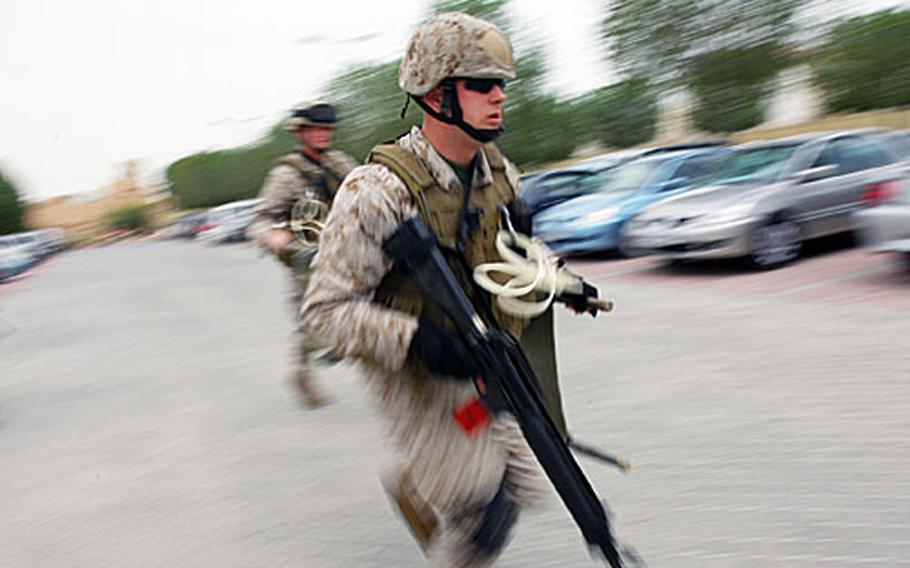 A U.S. Marine stationed at Naval Support Activity Bahrain rushes to the scene of a mock car explosion during a training exercise on the Navy base on Tuesday.