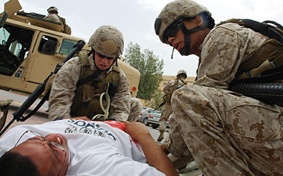 """U.S. Marines stationed at Naval Support Activity Bahrain treat a """"patient"""" during a training exercise """"Desert Sailor 07"""" on Tuesday. The exercise simulated a car explosion on the U.S. Navy base, with nearly two dozen people """"killed"""" and another nearly two dozen """"wounded."""""""