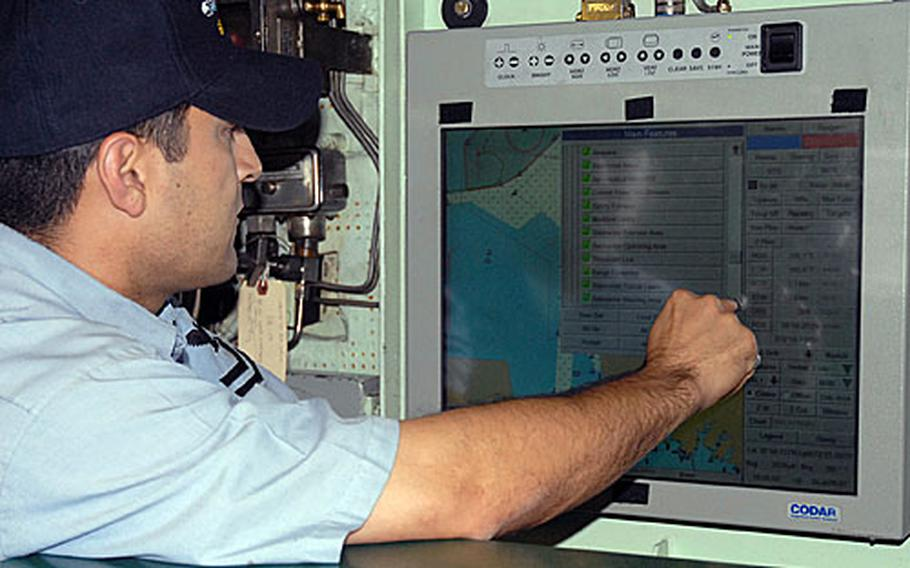 A sailor aboard the USS Oklahoma City familiarizes himself with the Voyage Management System. VMS is a combination of digital charts, constant global positioning system fixes, environmental sensors and electronic command and control to allow the submarine to eliminate many of the constraining aspects of navigation when using paper charts.