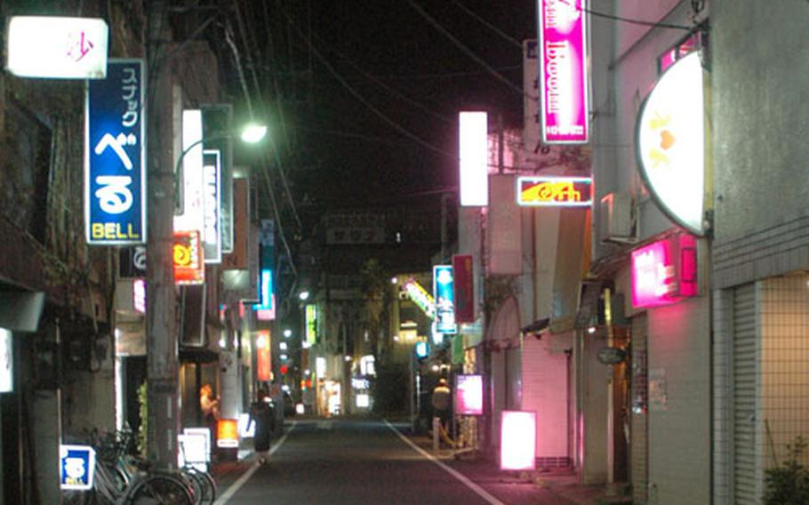 """""""Bar Row"""" in Fussa, Japan, is deserted at about 10:30 p.m. on a Friday night."""