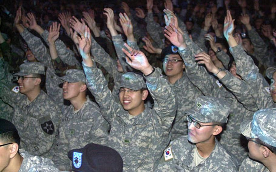 South Korean soldiers sway to the live music at a U.S./KATUSA friendship week concert at the Schoonover Bowl on Camp Casey Thursday night. The concert served to kick-off a Friendship Week that begins Monday in the camps north of Seoul.