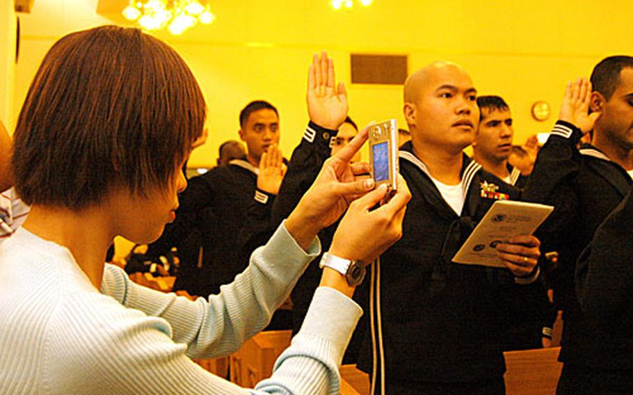 More and more non-citizen military members are taking advantage of the expedited, no cost naturalization process, according to U.S. Citizenship and Immigration Services. Friday's ceremony -- with 121 servicemembers from 34 countries -- was the biggest ceremony held to date at Yokosuka Naval Base.
