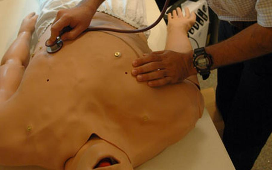 An Iraqi doctor listens for simulated signs of life in a computerized first-aid mannequin recently during a training session at Ibn Sina Hospital in Baghdad's Green Zone. The physician, who also works as a translator, agreed to be photographed but asked not to have his real name not be printed for security reasons.