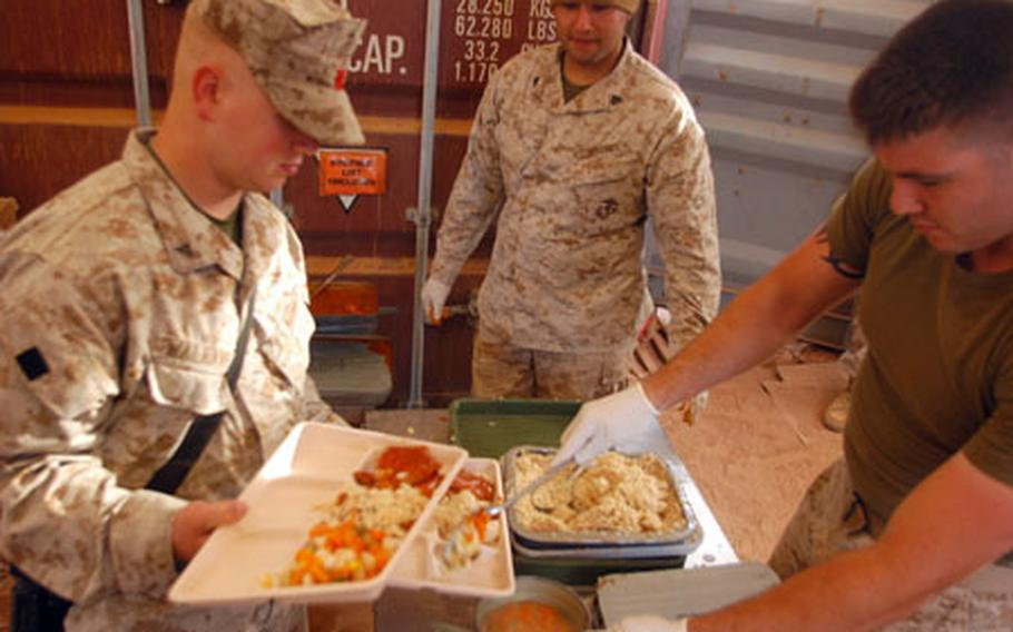 Lance Cpl. Matt Goldberg, right, of 2nd Battalion, 23rd Marine Regiment, and Sgt. Jesus Yepez, center, serve grub to Lance Cpl. Daniel Walraven, left, in the Logistic Support Area at Cap Draa Training Area in Morocco during African Lion 07, a joint training exercise between the U.S. and Moroccan militaries.