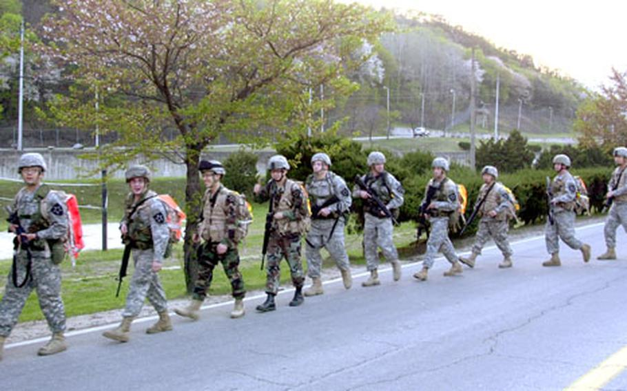 """Soldiers from the 2nd Infantry Division set off from the Camp Casey theater parking lot for the """"Manchu Mile,"""" a 25-mile overnight march. The 2nd Battalion, 9th Infantry Regiment's tradition commemorates a 1900 battle during China's Boxer Rebellion."""