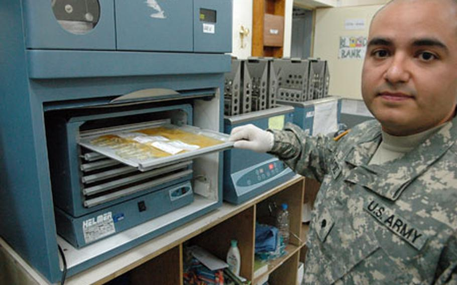 Spec. Carlos Martinez, 26, of Myrtle Beach, S.C., examines a tray of blood platelets in a blood agitator Friday. The machine rocks the blood clotting agents back and forth so that they can be stored without clotting.