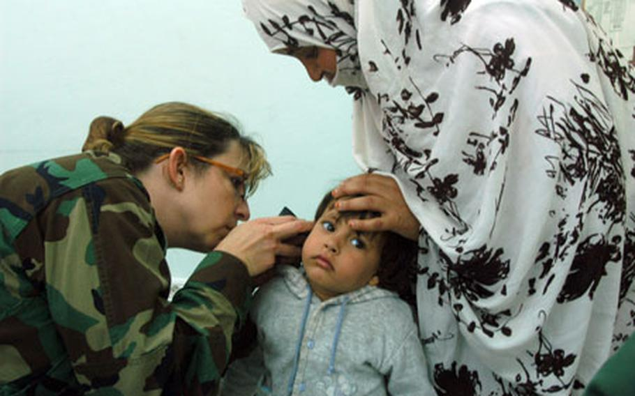Dr. (Maj.) Angela Wall examines the ear of a young patient during a humanitarian medical mission in Fask, Morocco, on April 22. The little girl was diagnosed with an infection and given antibiotics.
