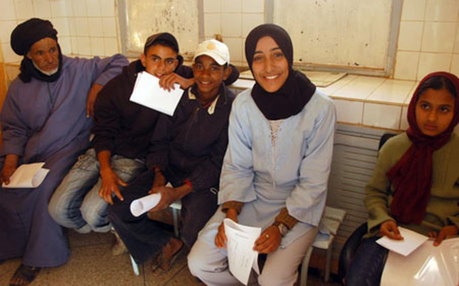 Latifa, 18, second from right, and others wait for dental appointments April 22 during a humanitarian medical mission in Fask, Morocco. She would later have her upper-right first molar removed.