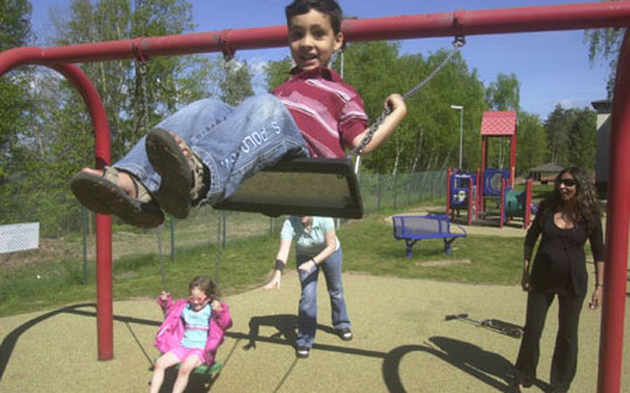 """Joey Hermansen, 5, gets a push on a swing at Landstuhl Regional Medical Center from his pregnant mother Salwa, right. Hermansen, whose husband works for the U.S. Embassy in Egypt, traveled to Landstuhl to give birth as part of the Storknest program. To the left is Hermansen's Storknest """"buddy"""" Tawny Campbell and Campbell's 4-year-old daughter, Ceilidhal."""