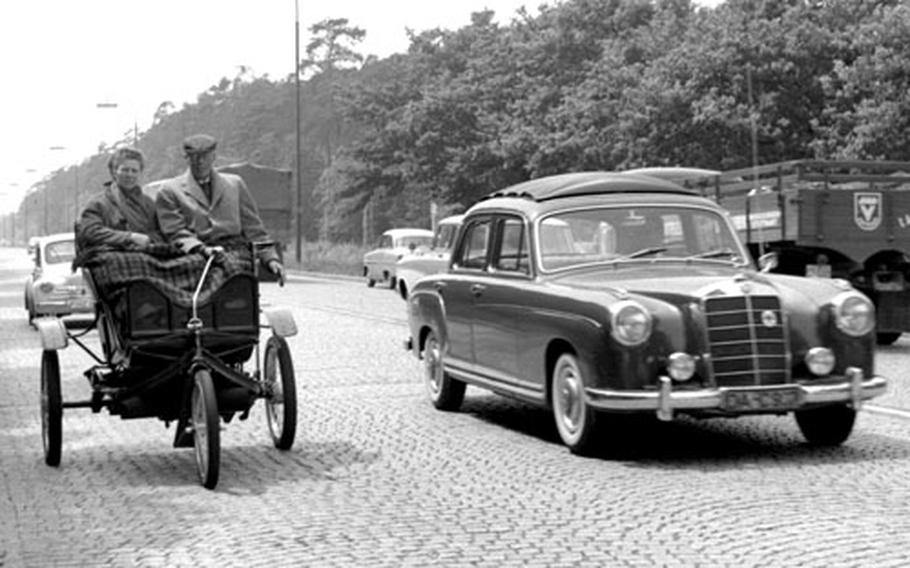 Modern vehicles roar past Roger and Elsie Johnson of Hadley, Mass. and their 1901 Knox in West Germany in June, 1960.