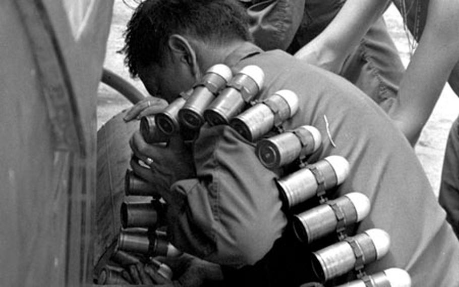 The ground crew loads ammunition onto a Cobra helicopter at Tay Ninh, South Vietnam, in 1971.