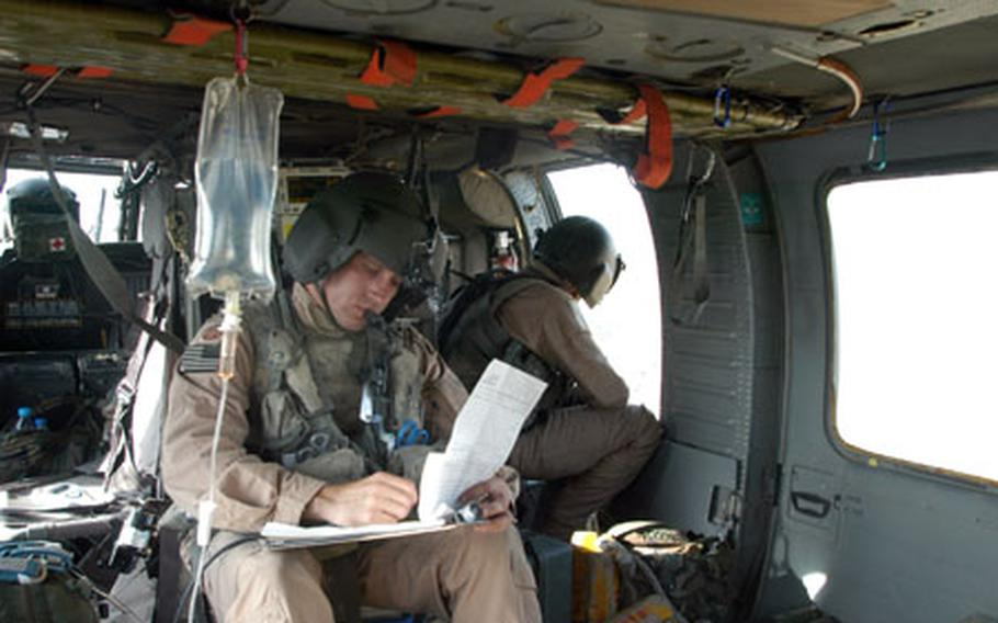 Staff Sgt. William Mudd, a combat medic with the 82nd Airborne Division, takes note during a medevac flight in Afghanistan.