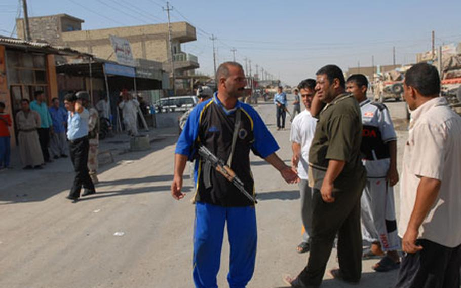 """An armed guard belonging to a group of Sunnis called """"Volunteers"""" helps provide security in Nasr Wa Salam, Iraq, a former al-Qaida stronghold in Iraq, during a visit by a Shiite government official last month. They are one of the groups of Iraqis working with coalition forces to provide protection in their own neighborhoods."""