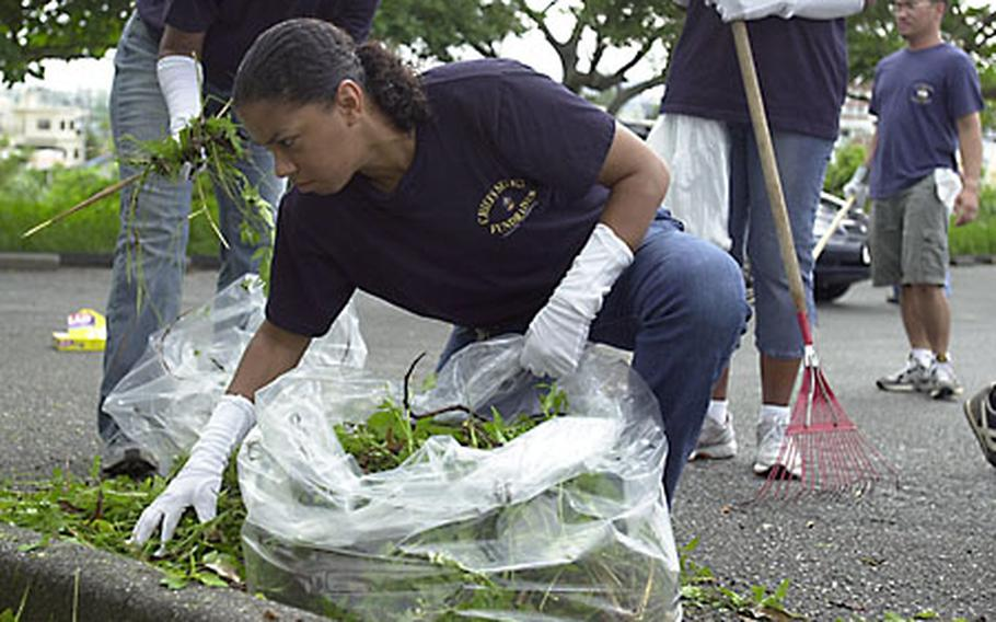 Chief Petty Officer (sel.) Edith LaFrazier, 36, from San Pablo, Calif., with Marine Wing Headquarters Squadron 1, bags leaves and grass at the Okinawa Children's Zoo in Okinawa City on Sunday. About 36 chief petty officer selectees were at the zoo cleaning up as part of a community-service project.