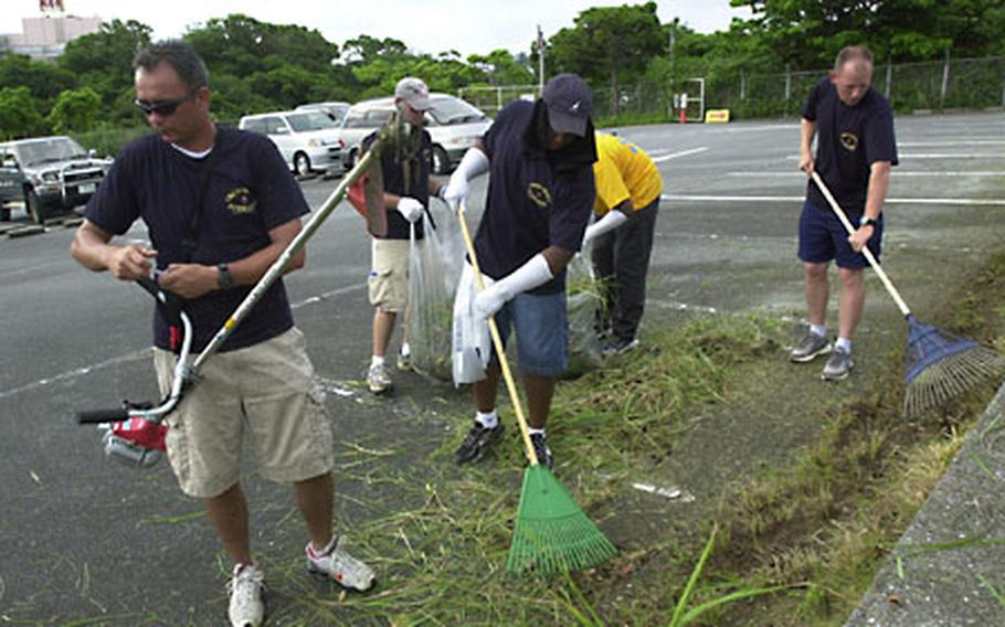 From left, Chief Petty Officer (sel.) Sean Rigg, 36, works a weed trimmer as Chief Petty Officers (sel.) Charlie Odom, 35, and Bruce Sims, 29, rake up cut grass at the Okinawa Children's Zoo parking lot in Okinawa City on Aug. 26.
