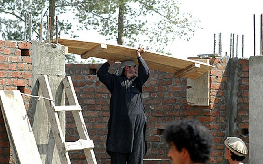 An Afghan laborer puts a roofing plank in place at the Mandozayi community center in eastern Afghanistan.