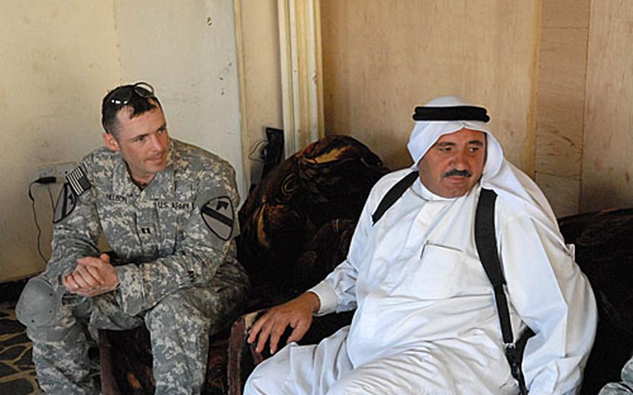 Sheikh Mohammed Faraj al-Alwani sits with Cpt. John Nelson of the 2nd Battalion, 5th Cavalry Regiment, as the two talk about several local infrastructure projects.