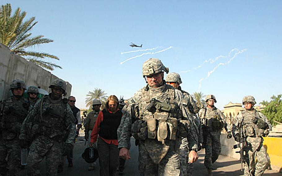 Col. Bannister leads troops and a small group of journalists to the Mutannabi Street book in eastern Baghdad market on Sunday. Apache helicopter gunships drop flares to draw off possible surface-to-air missles as they fly overhead.