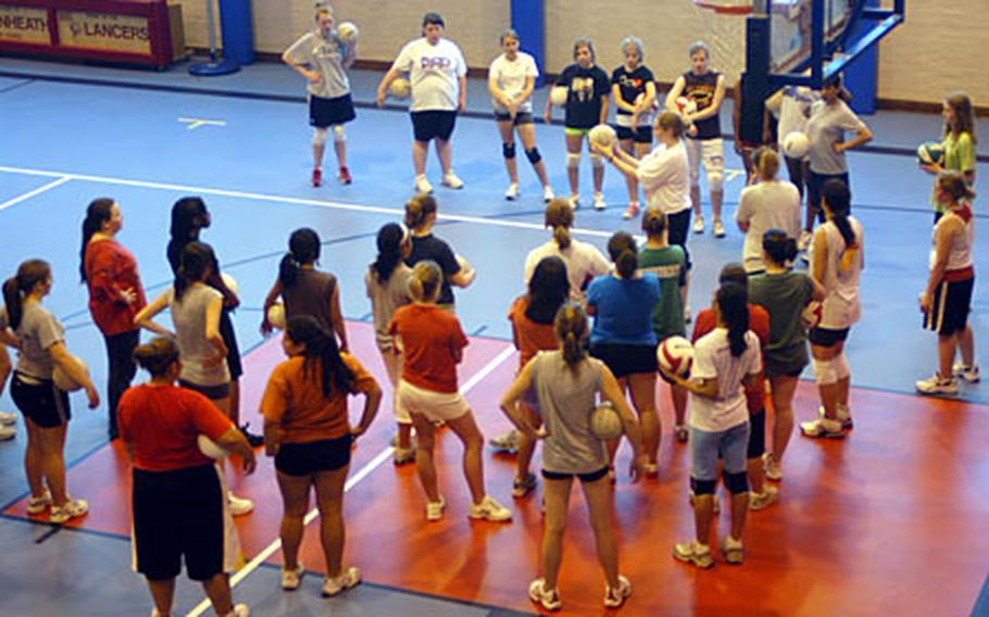 Lakenheath volleyball team hopefuls listen to head coach Kathy Schick during practice last week.