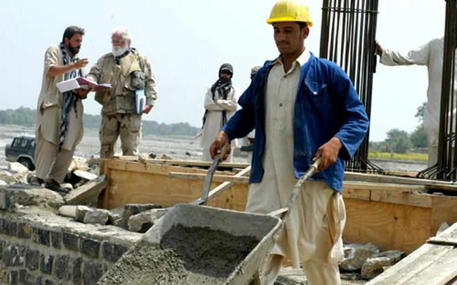 An Afghan worker pushes a wheelbarrow away from the Dadwal Bridge in Khost province while U.S. Army Corps of Engineer liaison Michael Butler discusses progress on the bridge with the Turkish contractor supervising the project.