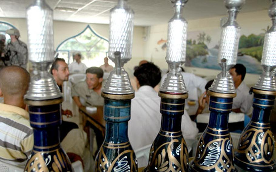 Men congregate and smoke tobacco from hookahs in The Boat, a restaurant on the banks of the Tigris River in Baghdad.