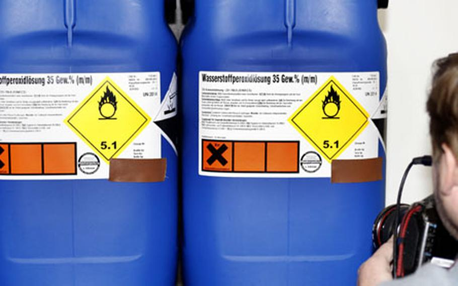 A photographer takes pictures of confiscated canisters labeled as hydrogen peroxide during a press conference in Karlsruhe on Wednesday.