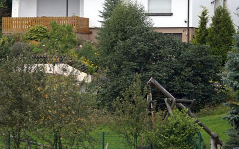 Cows graze in a field in front of a holiday home in Oberschledorn, Germany, where three men were arrested on suspicion of terrorism-related activities.