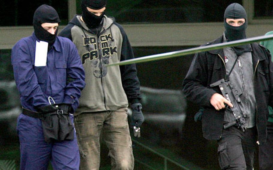 A man believed to be a terror suspect, left, is led away at the German Federal Court in Karlsruhe, Germany, on Wednesday.