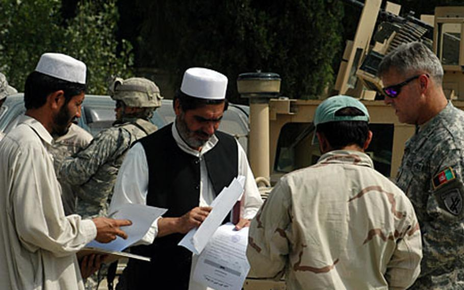 Maj. Steven Kieler, right, greets participants of a recent Khost province emergency management meeting.