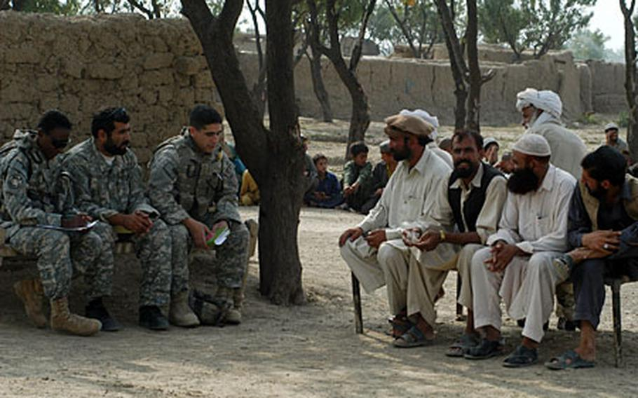 From left, Navy Cmdr. Adrienne J. Simmons, an Afghan interpreter and ensign Christopher Weis meet with elders from a camp that is home to roughly 1,000 refugees who now live in mud huts on land belonging to the Afghan Directorate of Agriculture.