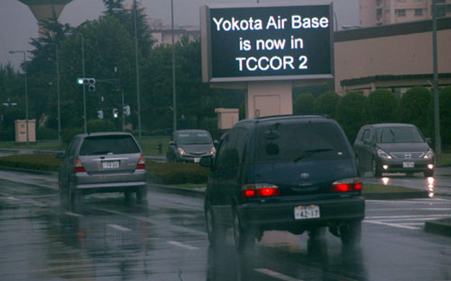 As rain falls Wednesday afternoon at Yokota Air Base, Japan, the video marquee on Airlift Avenue announces the latest Tropical Cyclone Condition of Readiness alert to passing motorists.