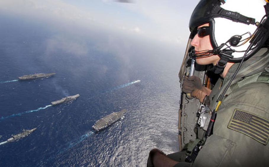 Aviation Warfare Systems Operator 3rd Class Christopher Bast, 21, from Temecula, Calf., watches from a U.S. Navy aircraft as naval ships from India, Australia, Japan, Singapore and the United States join for a group photograph in the Bay of Bengal during Exercise Malabar on Wednesday.