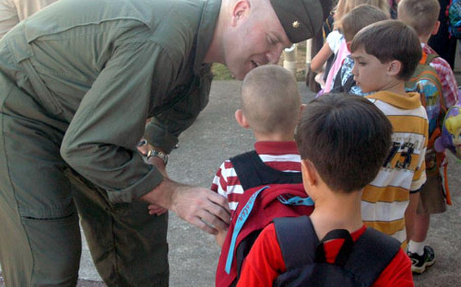"""Major T.B. """"Sweaty"""" Missler whispers words of encouragement to his son Logan, 5, on his first day of kindergarten at Killin Elementary School. Logan was one of about 800 students attending their first day of kindergarten Wednesday on Okinawa."""
