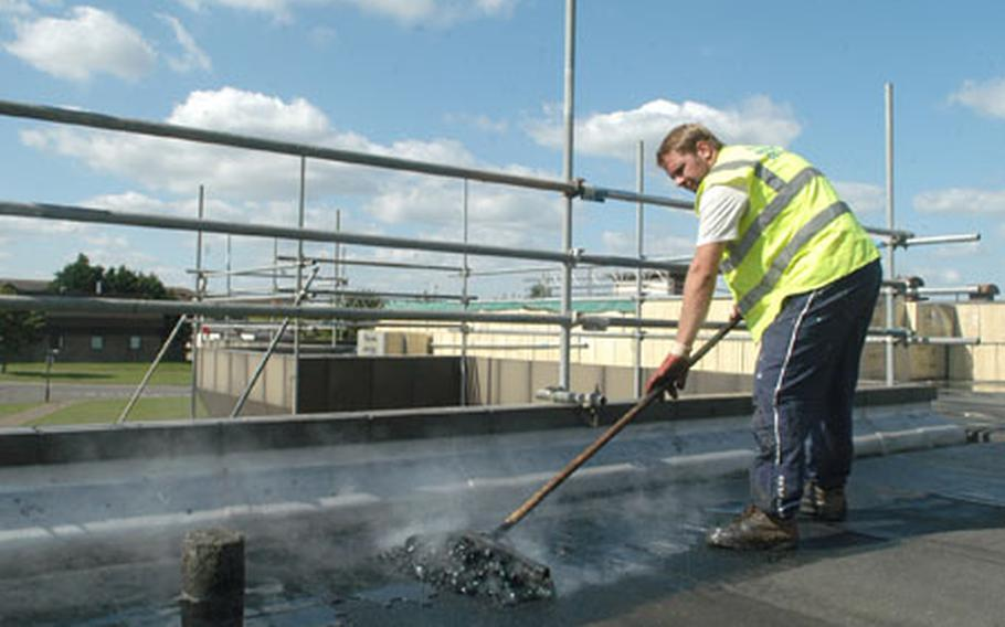 Scott Thurston, of Total Roofing Services, spreads hot tar on the roof of the Eagle's Landing building on RAF Lakenheath. This building and other Lakenheath facilities have had roof work done this summer, one of the wettest on record.
