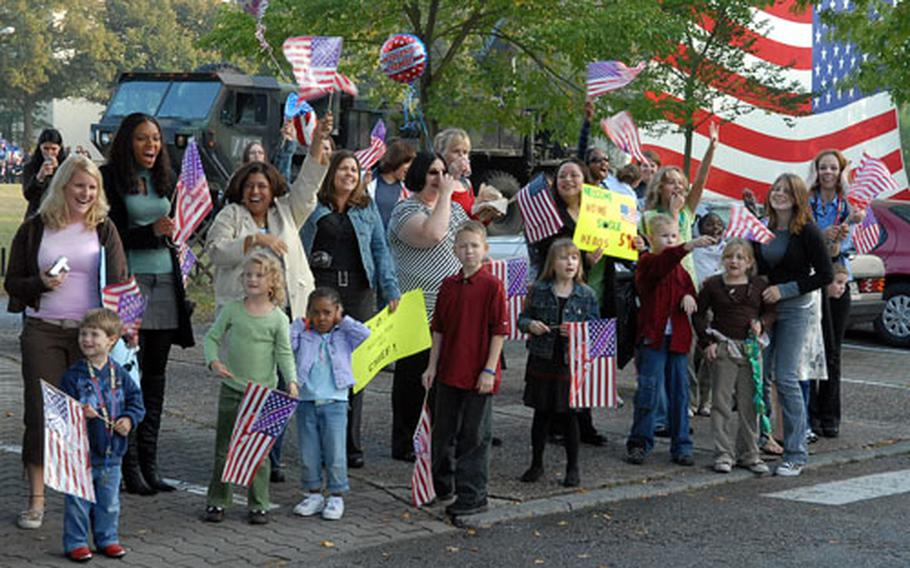 Family members and friends wave flags and cheer, as buses carrying about 200 soldiers of the 596th Maintenance Company arrive at Kelley Barracks in Darmstadt, Germany, on Thursday evening. The soldiers were returning from a deployment to Iraq.