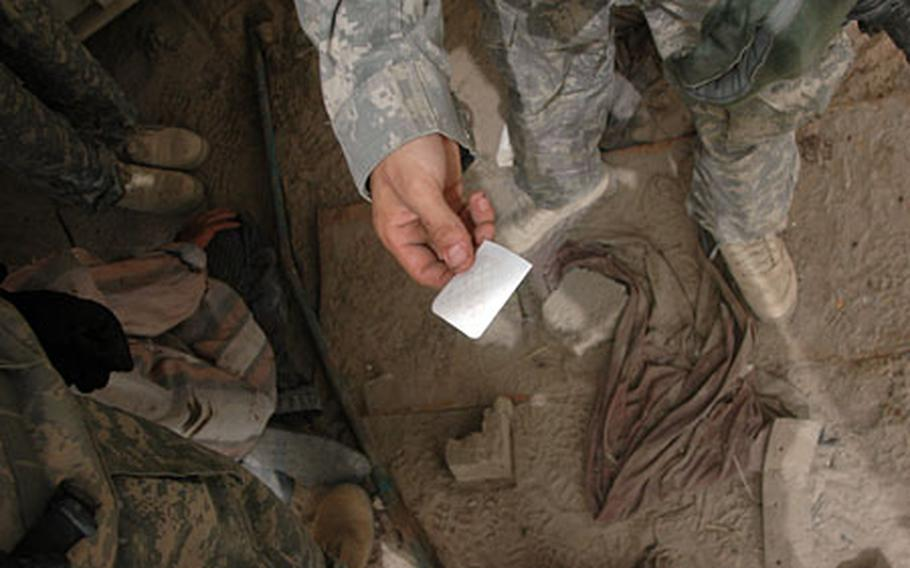 Soldiers from a roadside-bomb clearance team inspect a piece of explosives residue testing paper after it was rubbed on an Iraqi suspect's hands and sprayed for evidence. It came up negative.