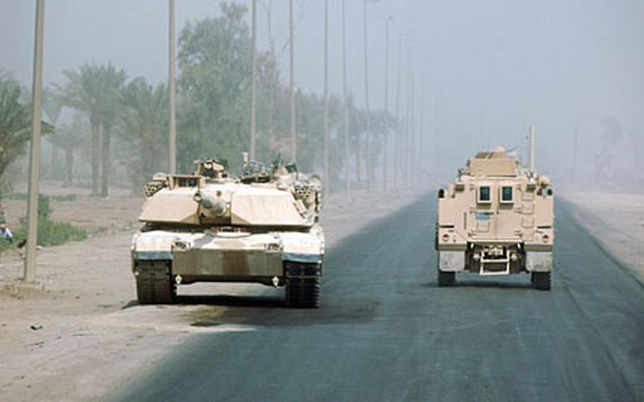 An Abrams tank and a heavily armored route-clearance vehicle pass each other on Route Pluto, a name given to a major highway, in eastern Baghdad. Five U.S. troops died on Pluto and Route Predator, which intersects with Pluto. Soldiers from the 1st Battalion, 8th Cavalry Regiment of the 1st Cavalry Division's 2nd Brigade patrolled the area for roadside bombs on Saturday.