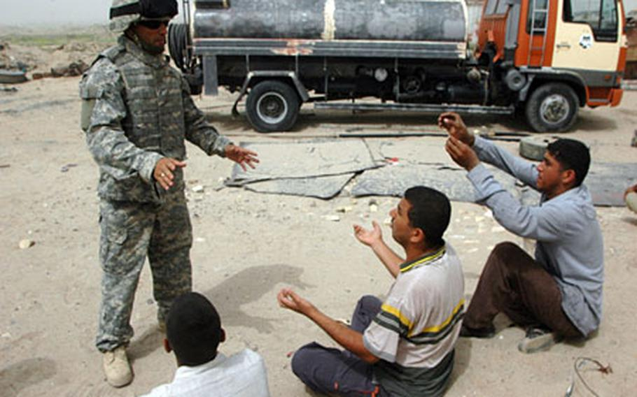 An U.S. forces interpreter speaks with several Iraqi suspects after a roadside bomb detonated near their business and workplace on what the U.S. refers to Route Pluto. No one was injured in the blast. Efforts have been stepped by the military to rid the major supply artery of explosives after two different incidents led to the deaths of five U.S. troops on Tuesday and Wednesday.