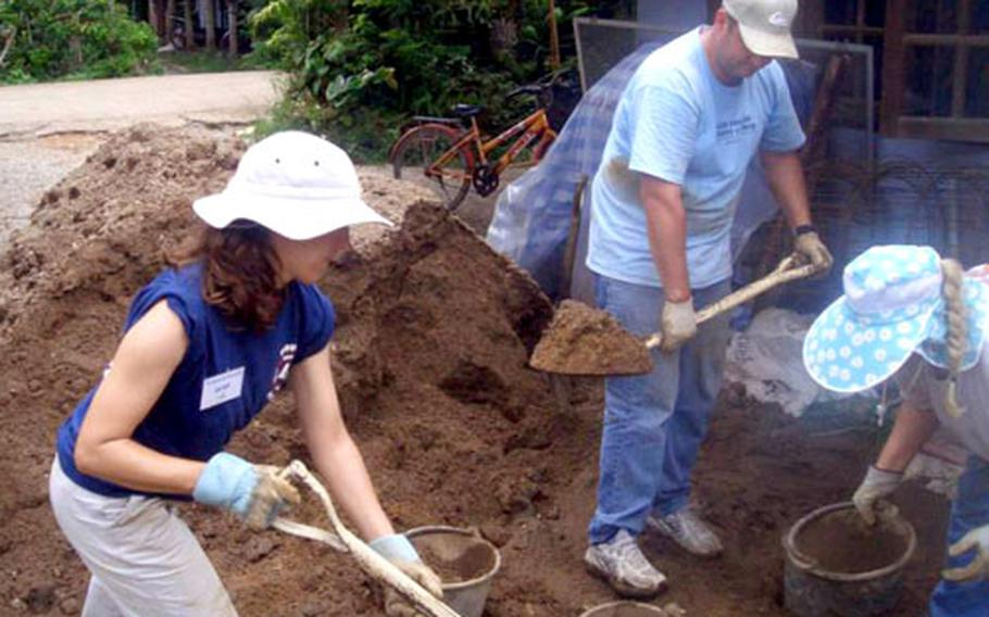 Volunteers from Yokota Air Base shovel dirt during a Habitat for Humanity project in Thailand.