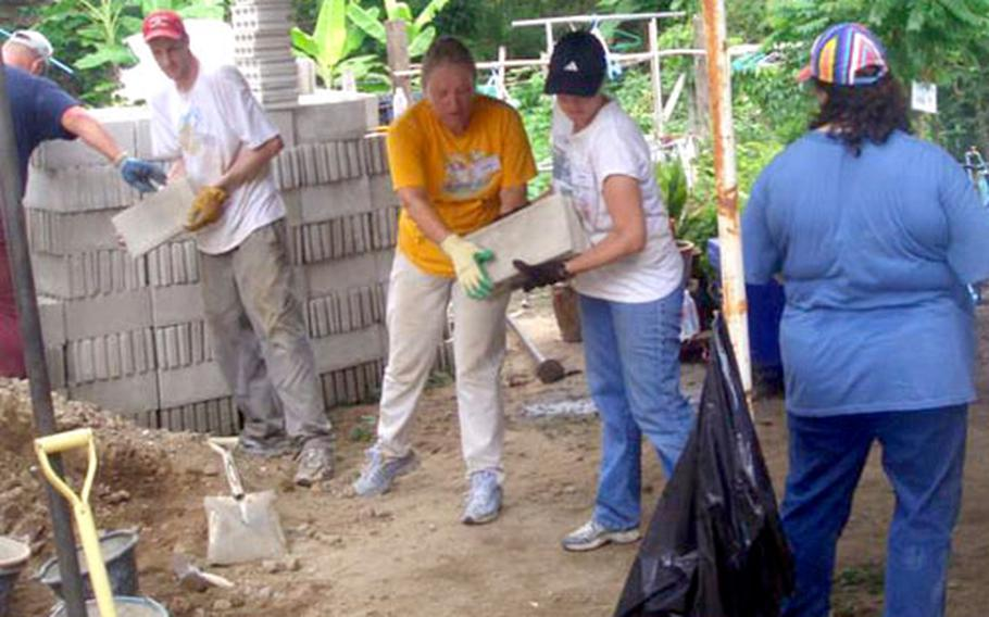 Yokota Air Base volunteers carry concrete blocks during a Habitat for Humanity project in Thailand.