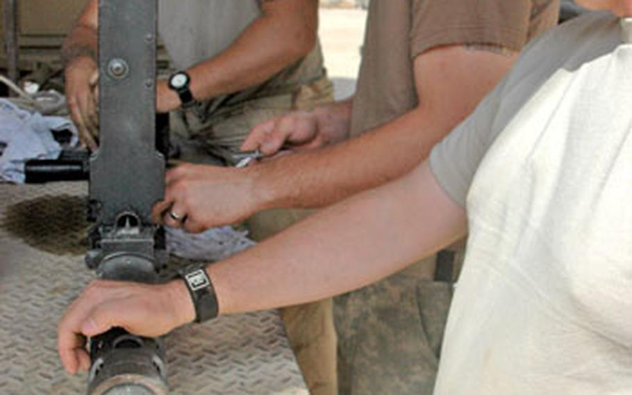 Reassembling a .50-caliber machine gun for re-positioning on a truck are, left to right, Spc. Marquis Goddard, 20, a native of Beaufort, S.C., Spc. Shawn Nelson, 23, of East Liverpool, Ohio, and Sgt. Anthony Cantrell, 35, from Longview, Wash.