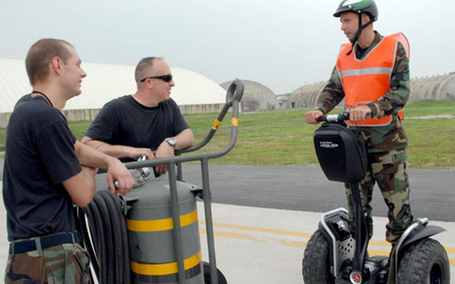 Maj. Lyle Drew, commander of the 51st Aircraft Maintenance Squadron at Osan Air Base, talks with two members of the squadron while operating one of 10 new Segways on base.