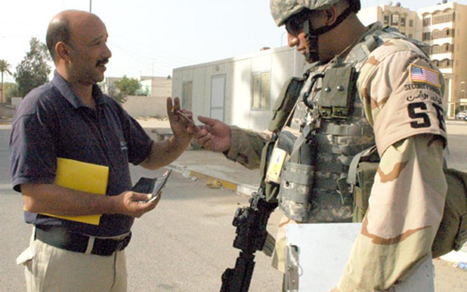 """U.S. Air Force Staff Sgt. Kawi Blake checks identification badges Sunday at the """"215 Apartments"""" within Baghdad's International Zone. Blake, 28, of Hilo, Hawaii, is part of the Air Force's 45-member IZ police force, which patrols the four-square-mile area."""