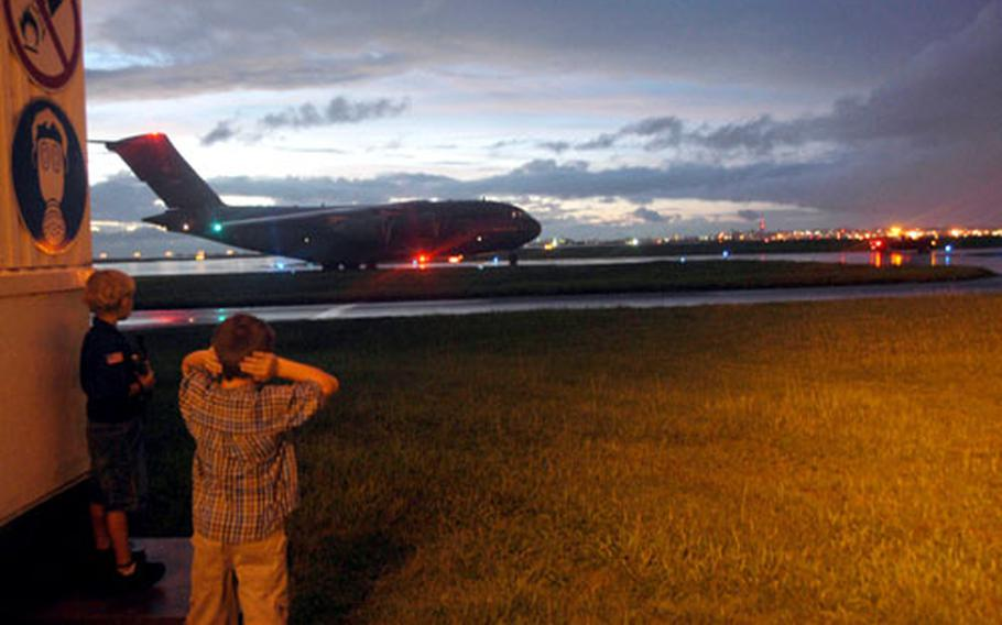 Jack, 7, covers his ears as a C-17 carrying his father taxis by down a runway at Kadena Air Base, Okinawa. On Monday, 14 men from the 31st Rescue Squadron, stationed at Kadena, returned from four months in Iraq.
